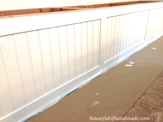 Paint is applied to the dining bench with storage.