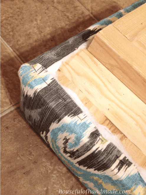 Close up of the staples on the removable top to the diy built in storage bench.