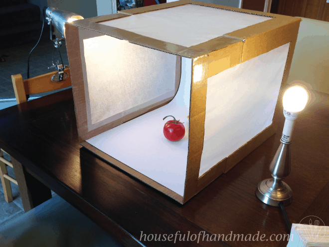 Use a homemade light box made out of household items to help you take  better photos