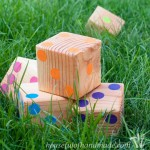 Set of 6 rainbow colored DIY yard dice made from 4x4s and craft paint.
