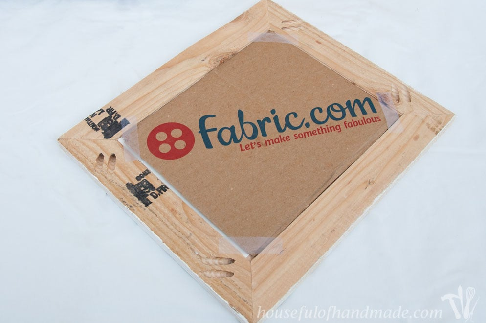back of diy rustic picture frame showing fabric.com cardboard taped to it