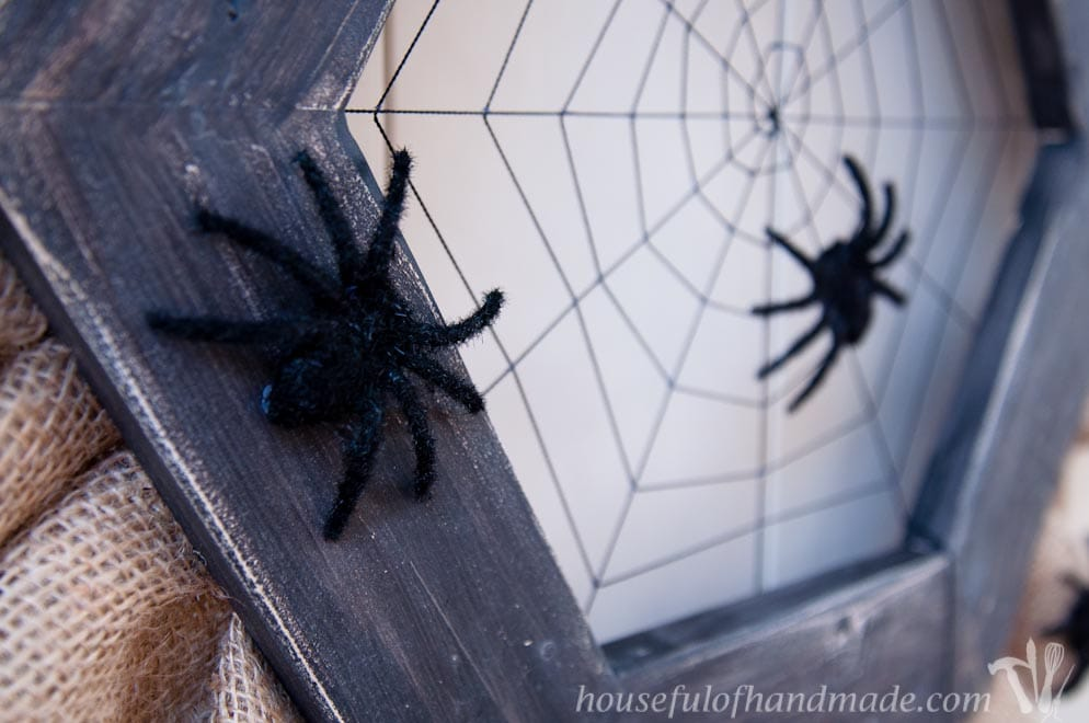 Fuzzy spiders on a wooden spider web wreath