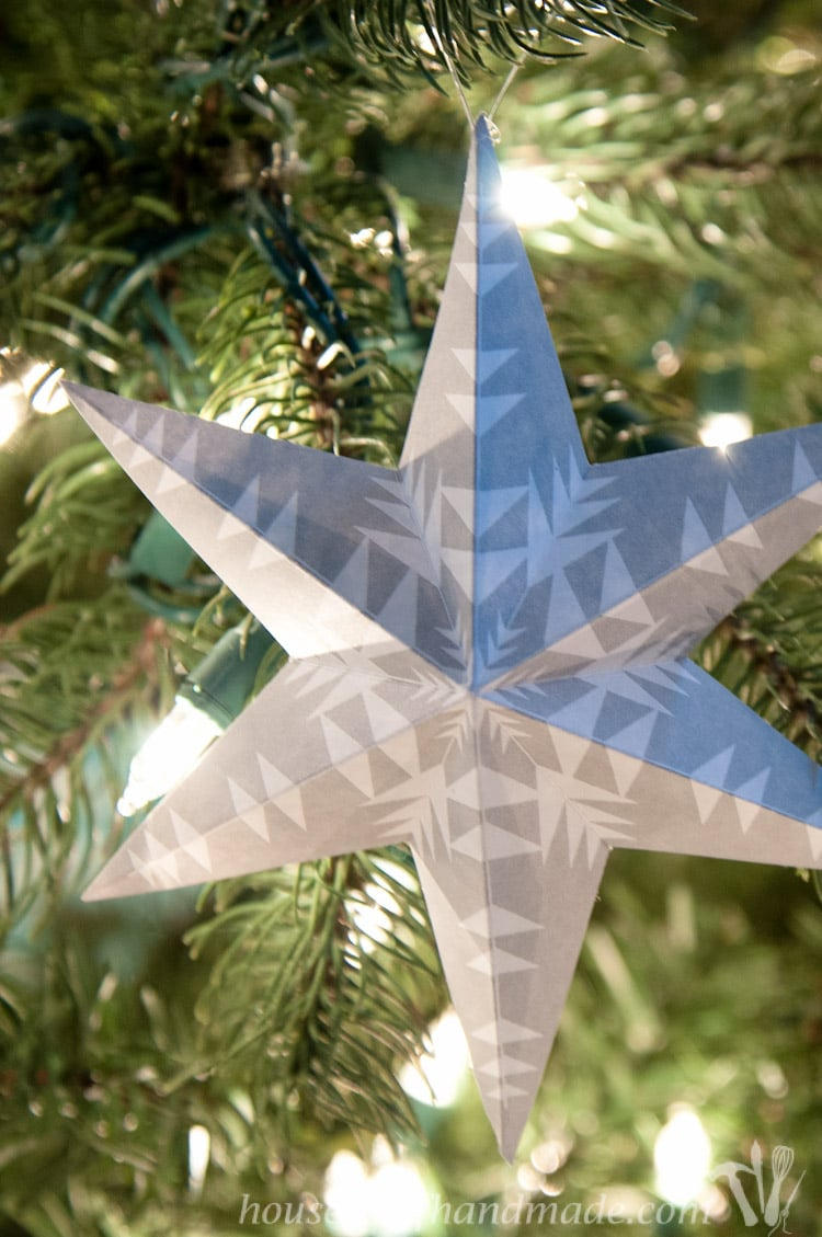 Gray 3D star with snowflake design on a paper Christmas ornament.