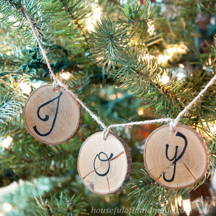 I love wood slice ornaments. Help them make a statement on your tree with these easy wood slice ornament banners. Beautiful and rustic.   Housefulofhandmade.com