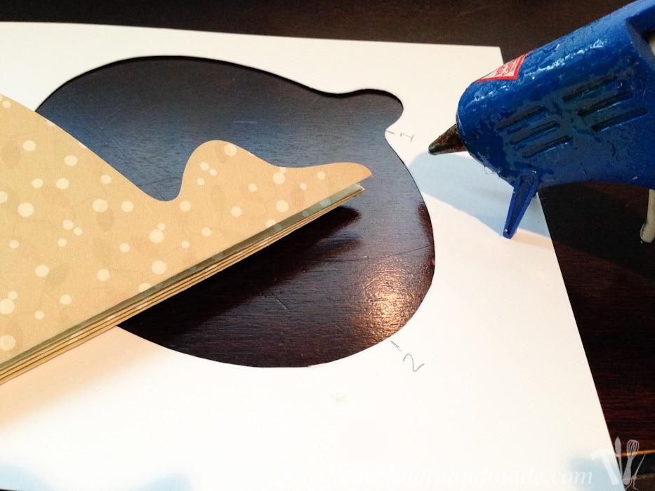 paper ornament cut out shown with hot glue gun.