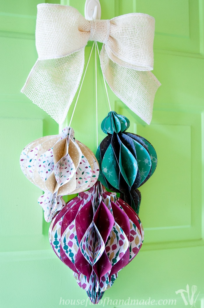 DIY giant paper ornament Christmas wreath hanging on front door from burlap bow.