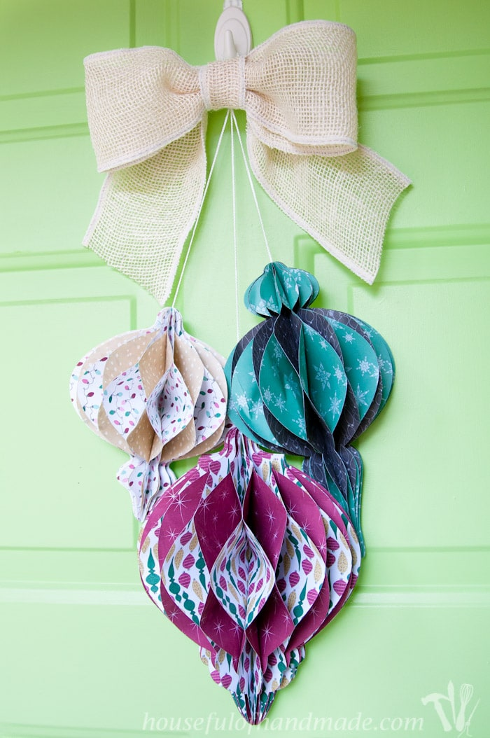 DIY giant paper ornament Christmas wreath with three ornaments showing on front door.