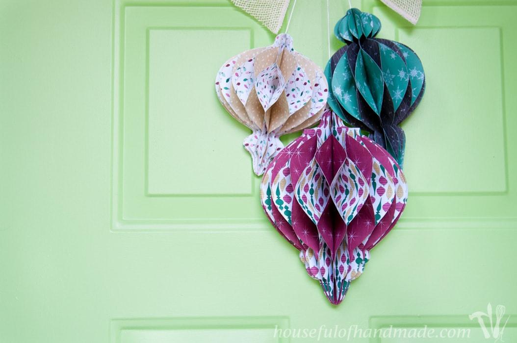 DIY giant paper ornament Christmas wreath hanging on front door.