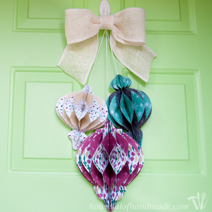 Beautiful DIY giant paper ornament Christmas wreath shown hanging on front door with burlap bow.