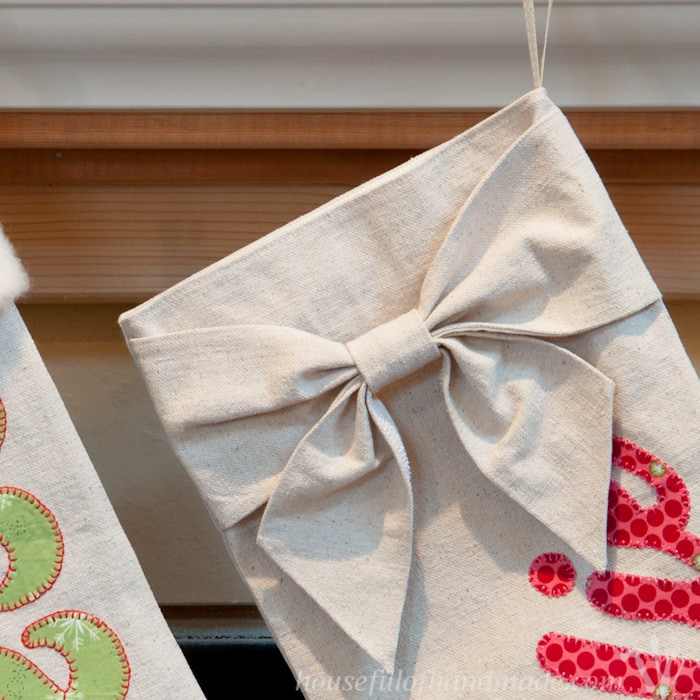 I love these beautiful DIY personalized drop cloth Christmas stockings. Using inexpensive materials and a few tips to appliqué everyone's names on their stocking make these beautiful and long lasting Christmas stockings. | Housefulofhandmade.com