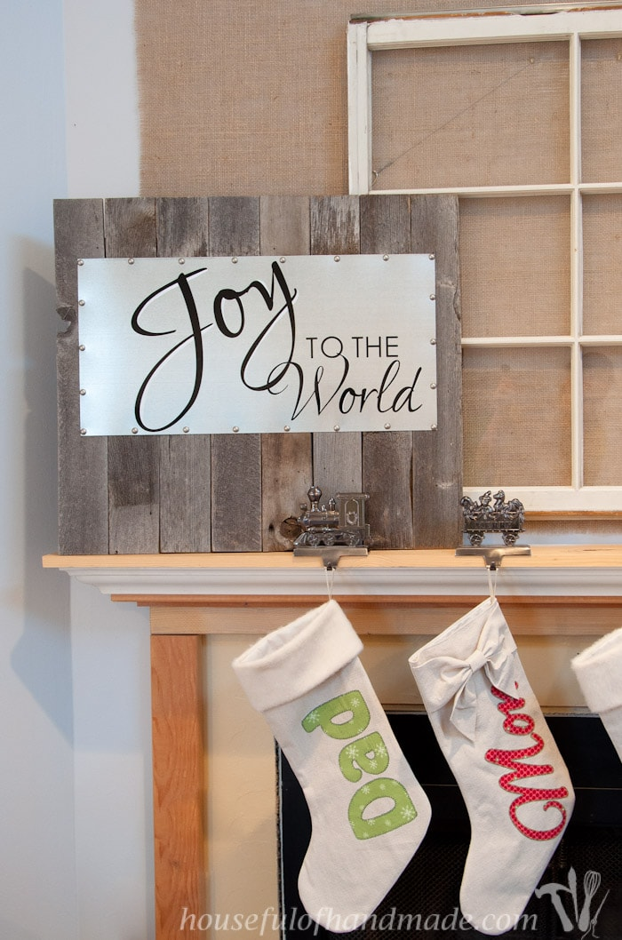 reclaimed wood and steel Christmas sign shown on mantel with stocking holders and two stockings