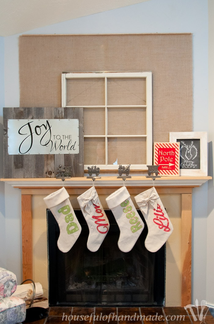 reclaimed wood and steel Christmas sign shown on fireplace mantel with four hanging stockings.