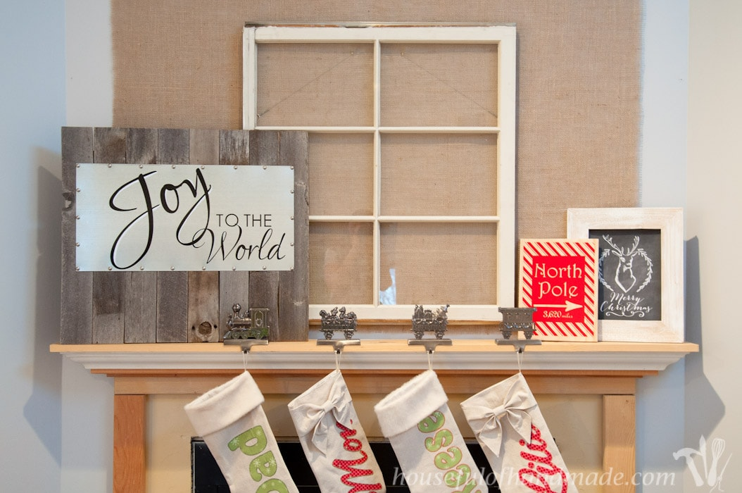 DIY reclaimed wood and steel Christmas sign displayed on fireplace mantel with old window and stockings.