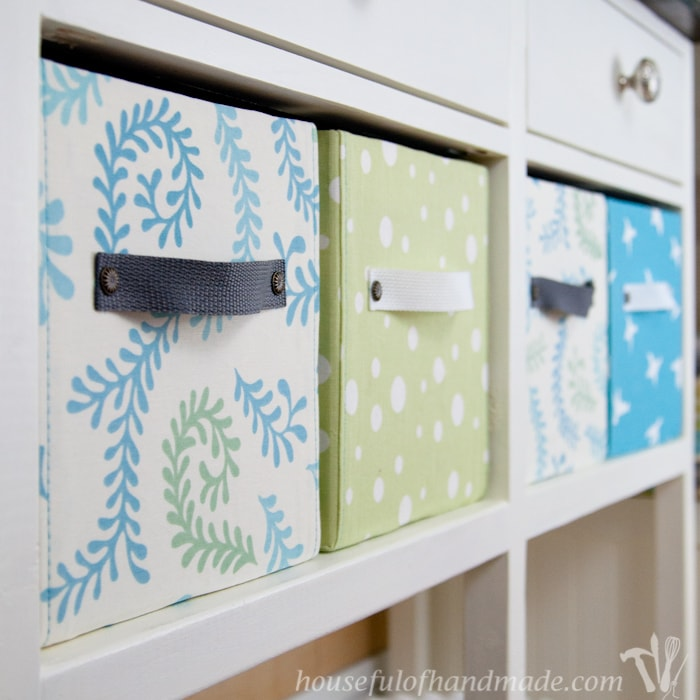 Easy DIY fabric storage boxes four shown on book case.