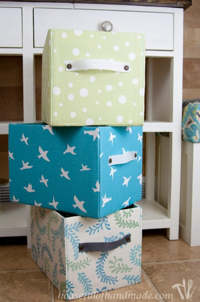 Cardboard boxes covered in fabric to make beautiful DIY storage boxes.