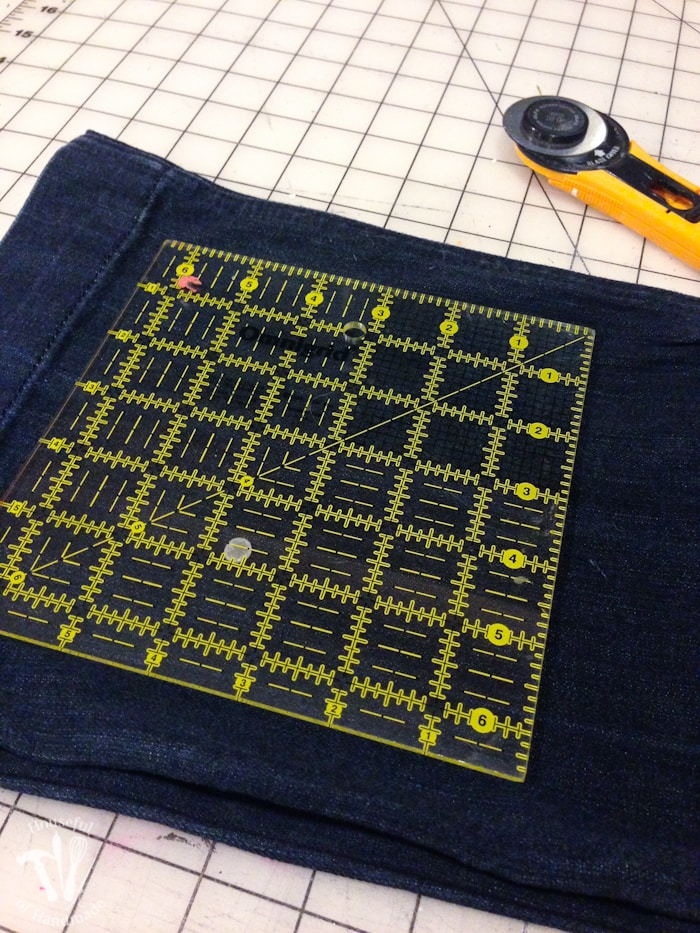 6 1/2 inch square quilt ruler and a rotary cutter on jeans before cutting