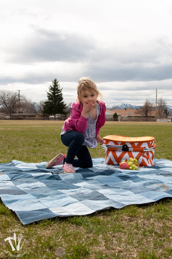 Young girl eating fruit on a Water-resistant upcycled jeans picnic blanket showing the quilted pattern