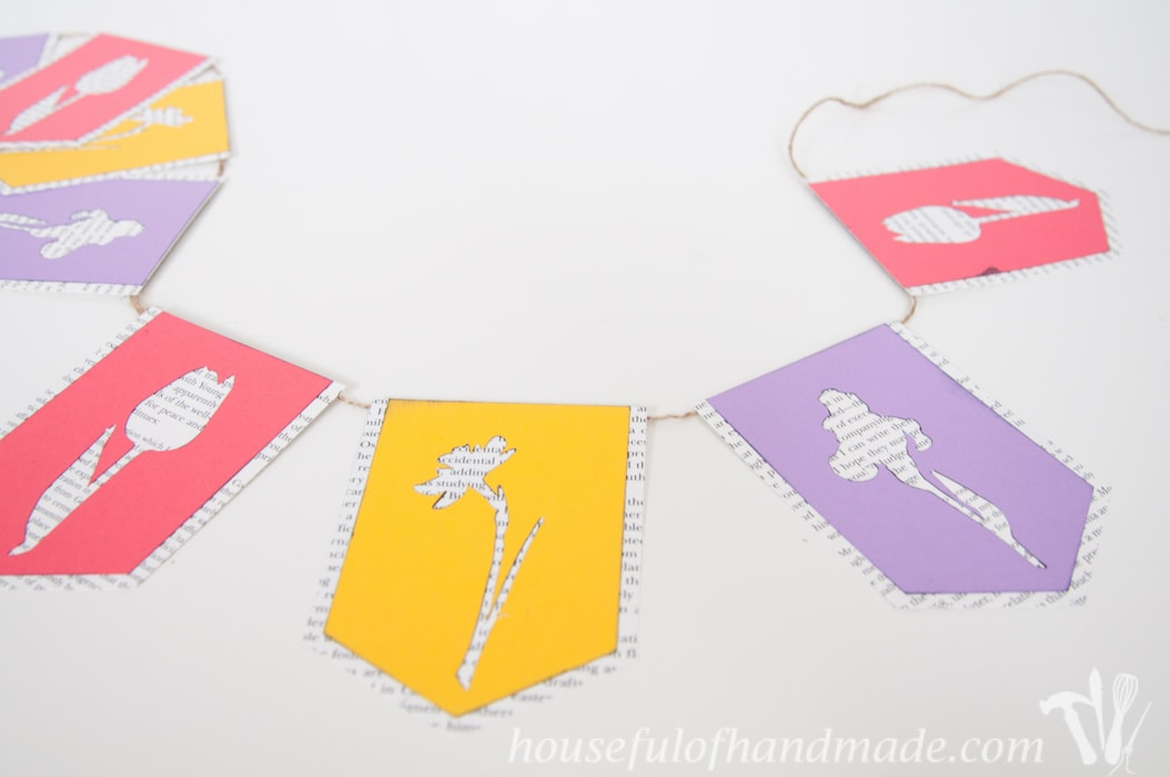 I love using banners to decorate. Create a beautiful spring flower & book page banner with this tutorial and free digital cut file.   Housefulofhandmade.com