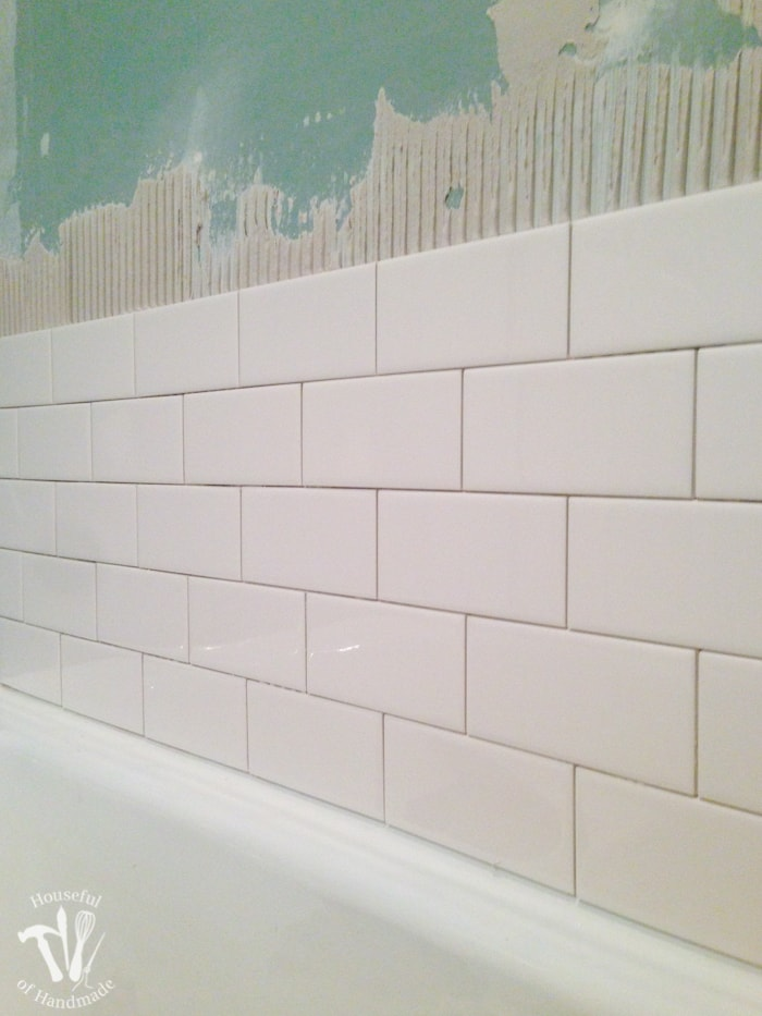 Bathtub surround being tiled with individual subway tiles.