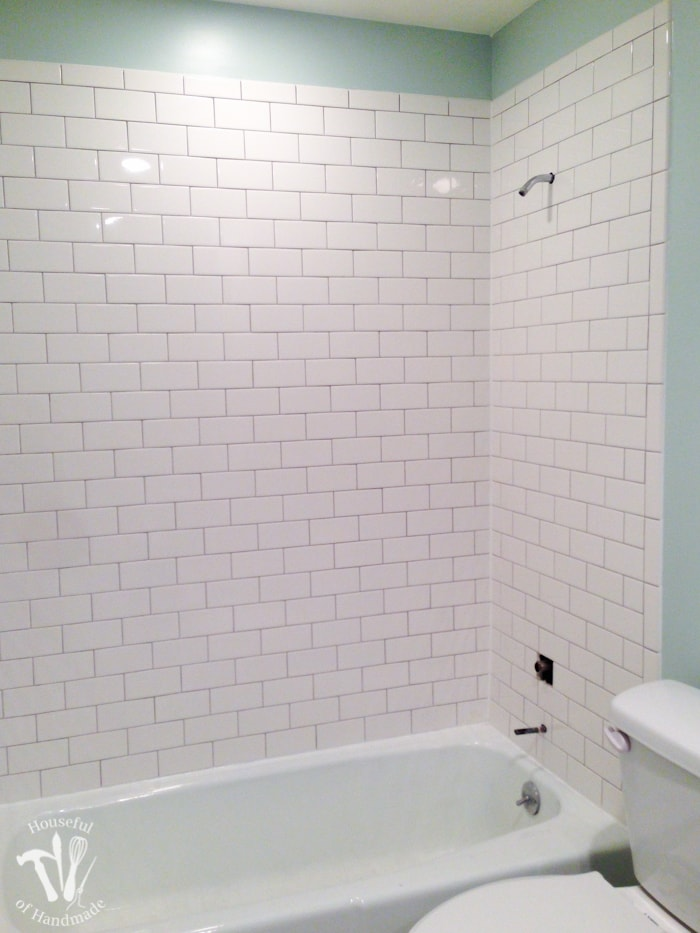 Bath tub surround tiled with 3x6 individual white ceramic subway tiles and grouted with a medium gray grout.