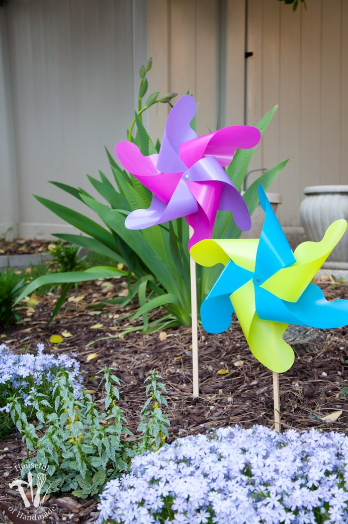set of two completed pinwheels in the garden one is pink and purple and one is yellow and blue