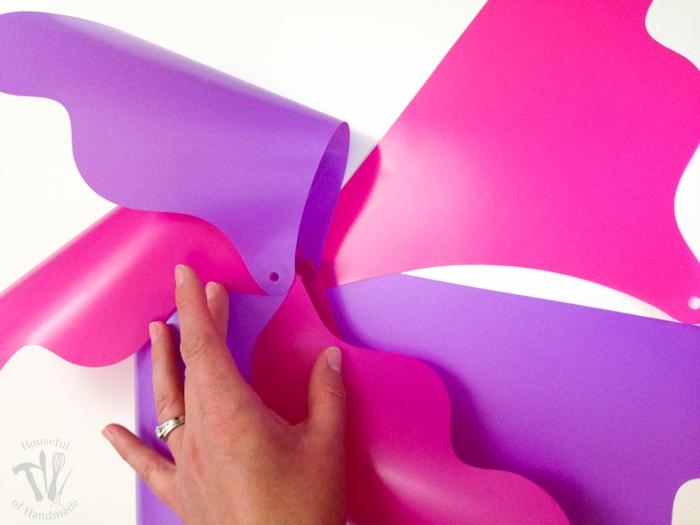 pink and purple individual pinwheels being put together with ladies hand glueing the pinwheel