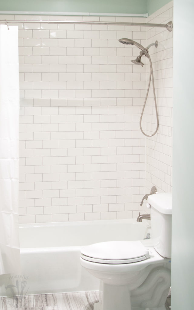 Tub and shower area tiled with classic white subway tiles and a white shower curtain.