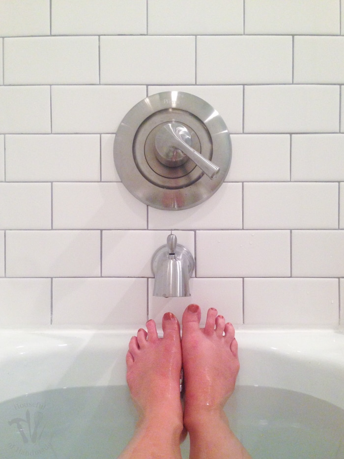 Feet sticking out of the bathtub in front of the faucet and subway tile surround.