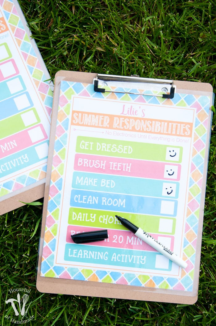 two clipboards shown on grass with free printable summer chore chart attached and an uncapped pen on top of printable