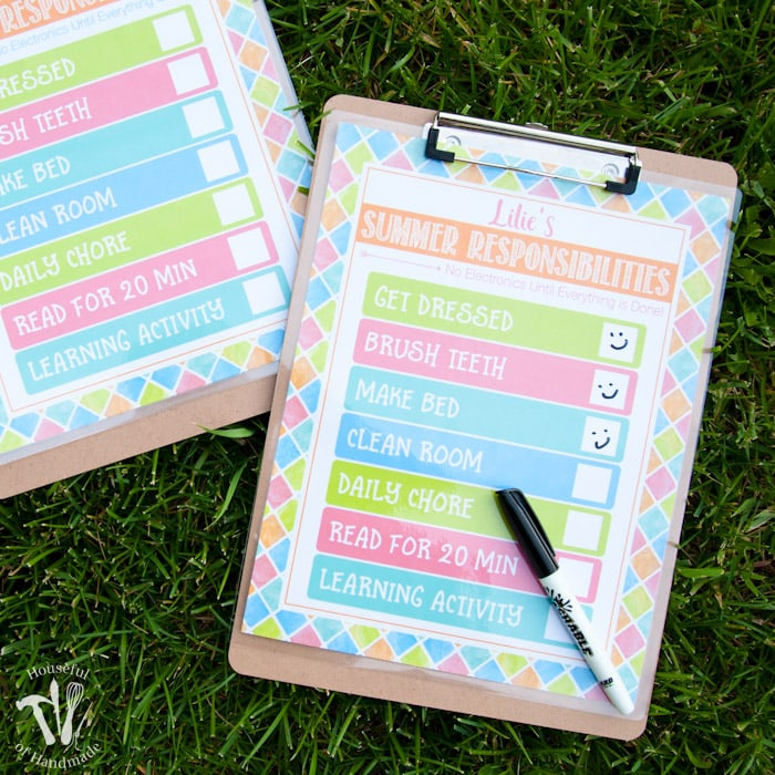 clipboard and pen with free printable summer chore chart on grass