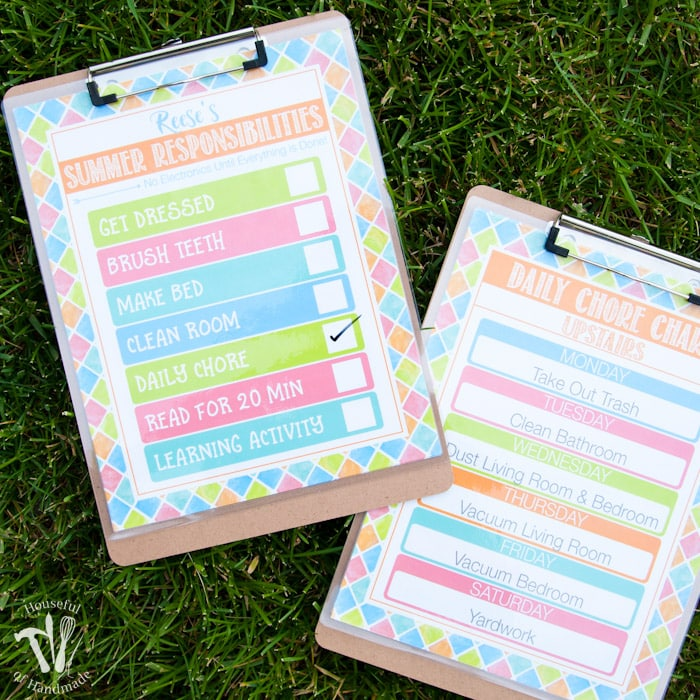 two clipboards on grass with free printable summer chore charts attached to clipboards