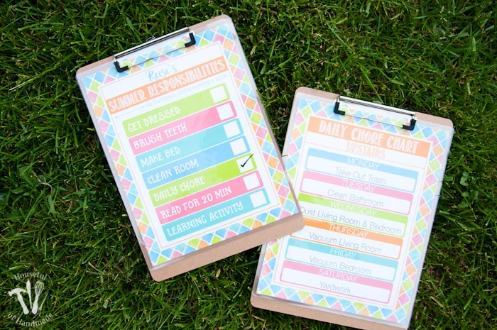 set of two clipboards shown on grass with free printable summer chore charts attached