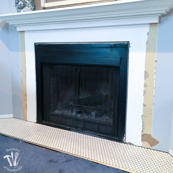 I'm working on updating a boring fireplace with a farmhouse style starting with tiling the fireplace hearth. The fireplace will be surrounded with beautiful white hexagon tiles with a gray grout. A wonderful update for only $100. | Housefulofhandmade.com