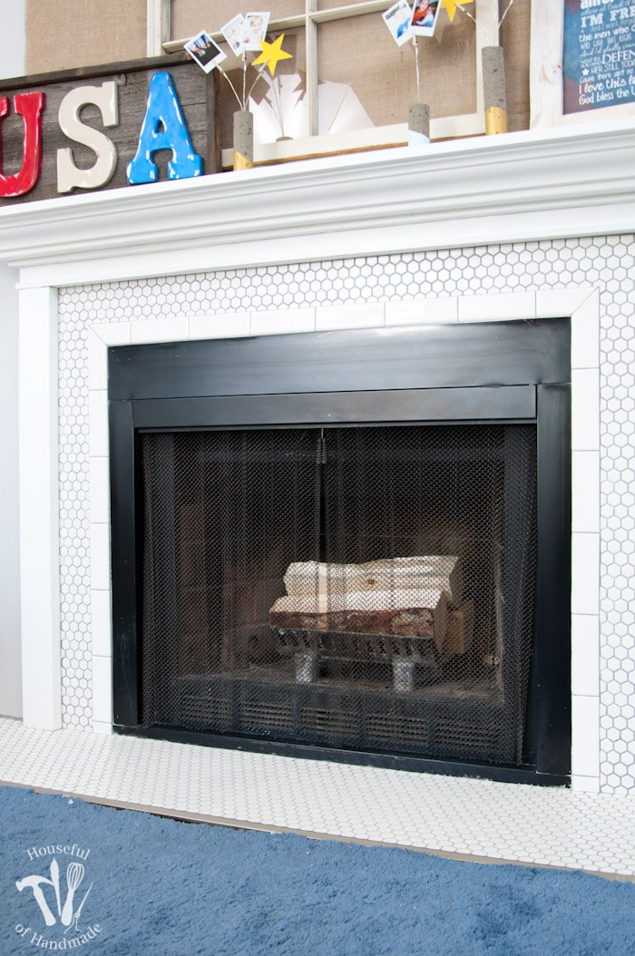 I love this vintage inspired farmhouse fireplace. DIY your own fireplace with new white hexagon tile on a budget. Love the white tiles and gray grout. Farmhouse fireplace reveal from Housefulofhandmade.com