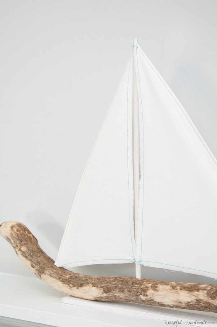 I love coastal decor! If you've ever skipped making your favorite driftwood project because you don't live by the ocean, no need for that anymore. Check out the tutorial for this DIY driftwood sailboat decor and find out where she found driftwood in a land locked state. | Housefulofhandmade.com