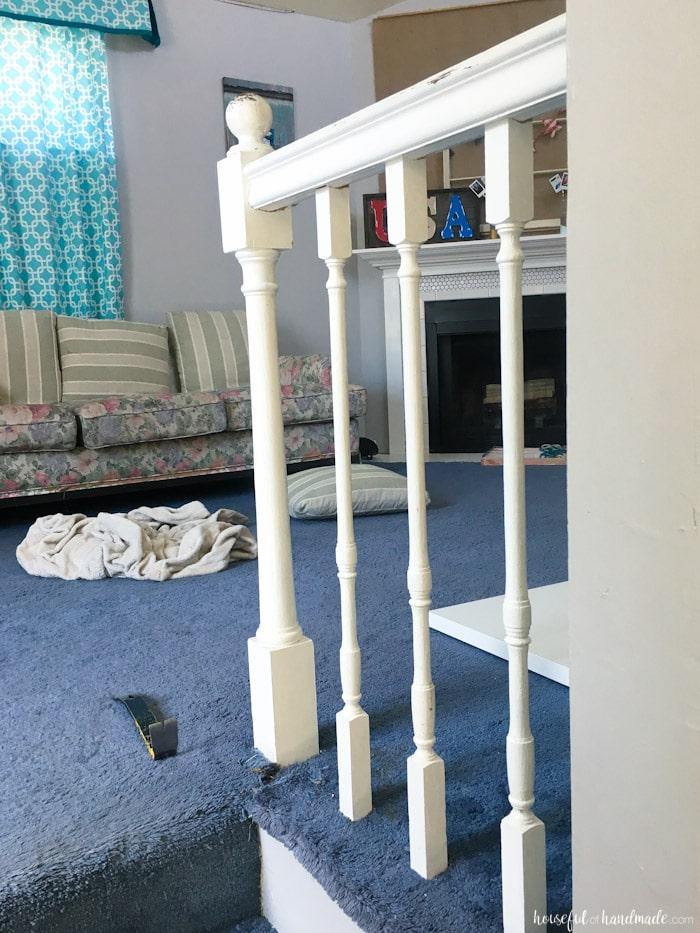 old builder grade railings in white shown in living room