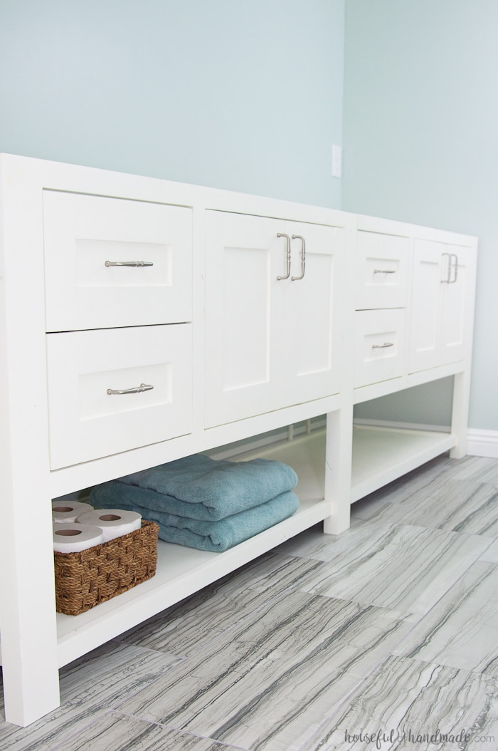 White mission style 8' bathroom vanity with open bottom shelf in bathroom wiht greenish gray walls and gray 12x24 tiles.