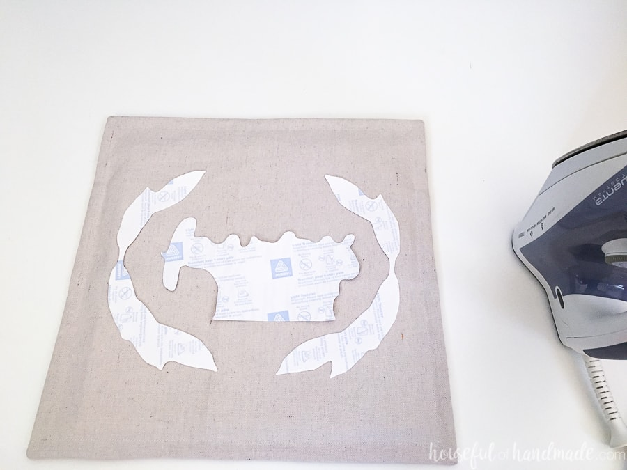 Printable transfer cut out on a decorative pillow before ironing.