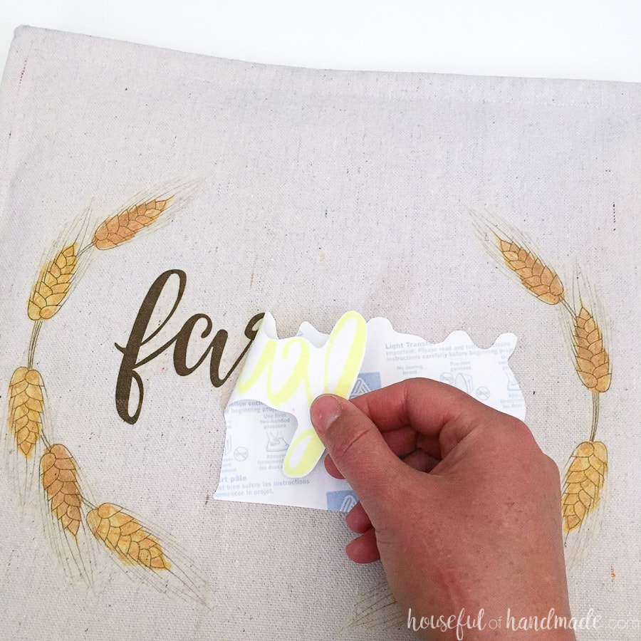 Carefully peeling off the backing of the iron on transfer to reveal the decorate pillow design.