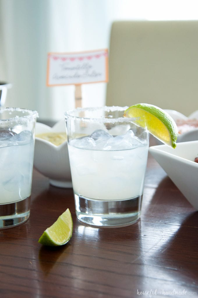 salt rimmed glasses with margarita and limes with salsa in the back ground at a Salsa & Margaritas Adult Birthday Party