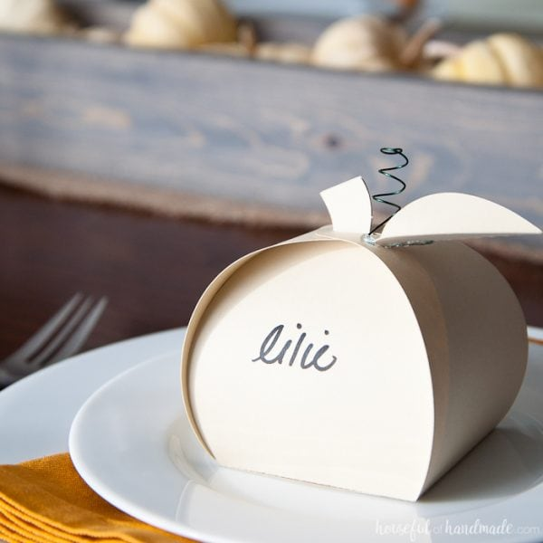 Make Thanksgiving extra festive with these easy Thanksgiving place cards that can be filled with treats for an easy appetizer. These paper pumpkin boxes are easy to make and will leave your guests feeling extra special this holiday season. | Housefulofhandmade.com