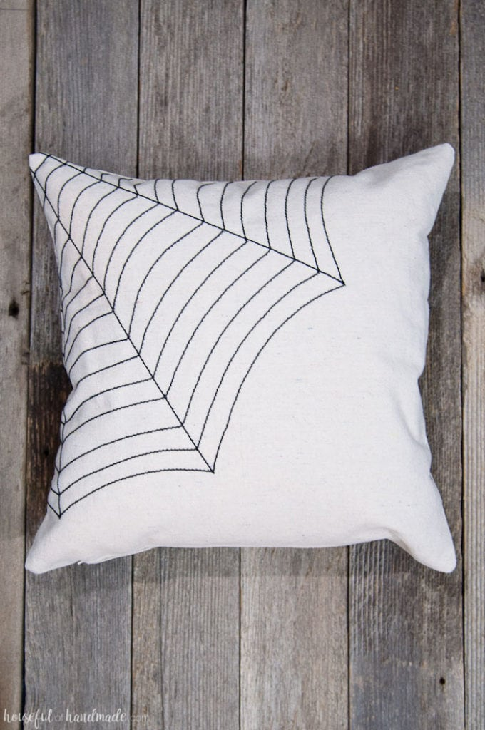 Love this simple pillow for Halloween! Celebrate October with this easy DIY farmhouse style spiderweb throw pillow made out of drop cloth and nylon string. It's simple rustic decor that will fit in with your current decor, but with a spooky touch. | Housefulofhandmade.com