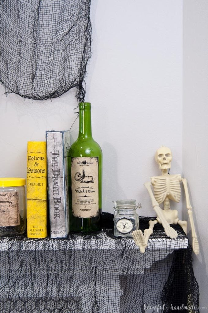 I love this mantle decor! Create a spooky apothecary Halloween mantle with easy DIY decorations. Spooky apothecary jars, bloody candles, and potions books make this the perfect spooky Halloween decor. | Housefulofhandmade.com