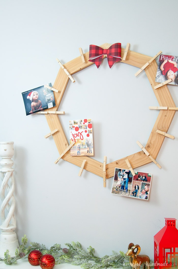 diy rustic farmhouse style Christmas card holder hanging on wall with photo cards