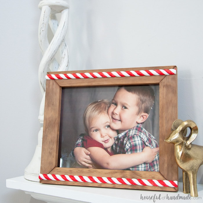 This is the such a great way to display Christmas memories! Make an easy rustic candy cane picture frame to add a little holiday spirit to your family pictures. Also make a great homemade gift for the season. | Housefulofhandmade.com