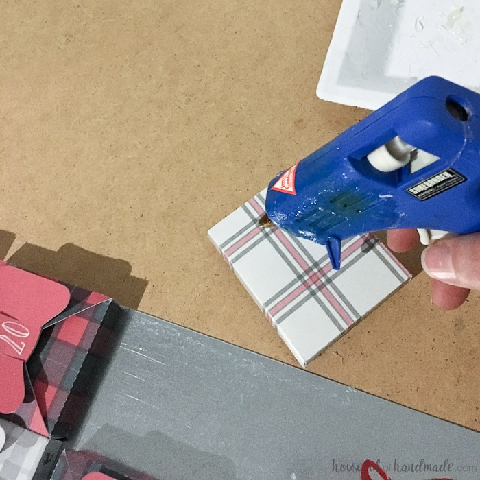 hot glue gun being used on buffalo check paper box.