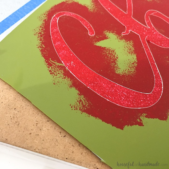 close up of red painted Christmas stencil for advent calendar.