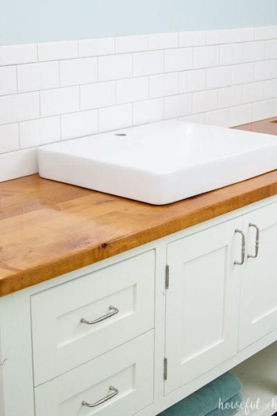 White mission style DIY bathroom vanity with wood vanity top and square vessel sinks.