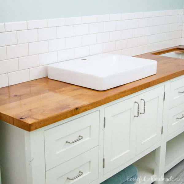 White mission style DIY bathroom vanity with wood vanity top and square vessel sinks.