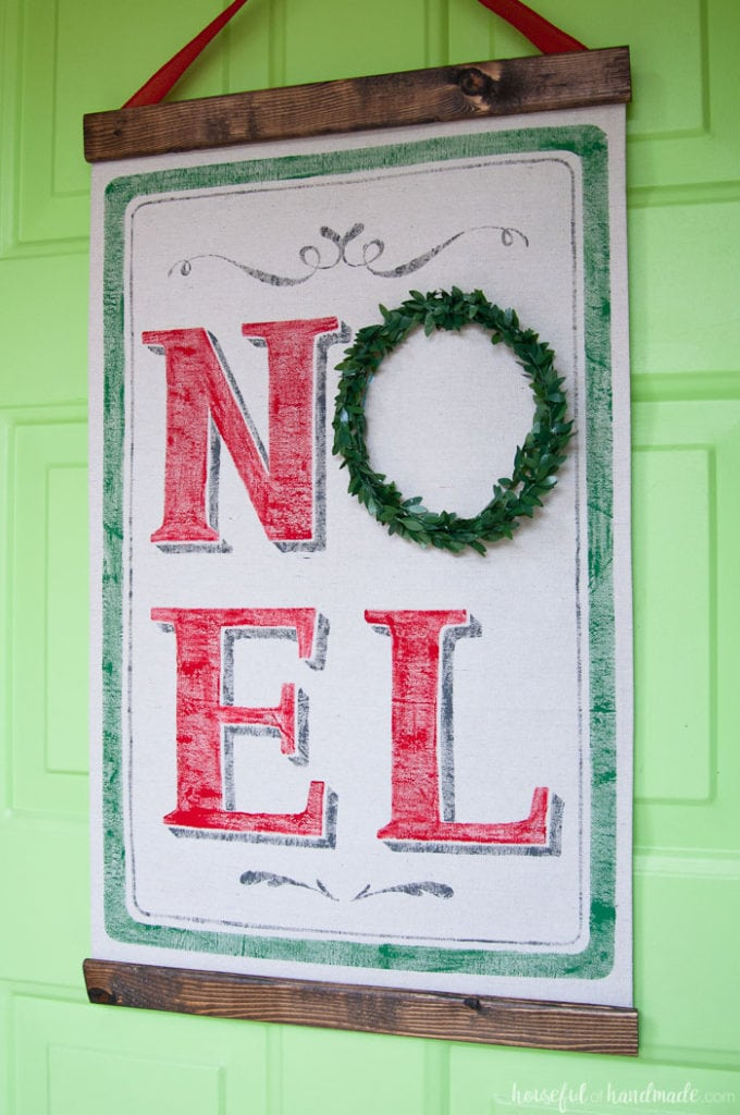 close up of Noel Christmas scroll hanging on green door